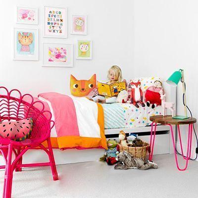 Niña leyendo en su cuarto rodeada de muñecos de tela