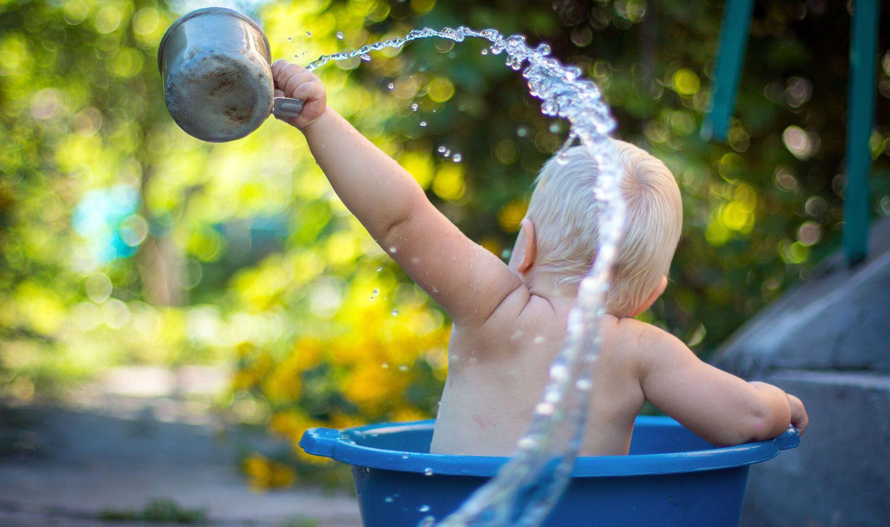Bebé bañándose en palangana