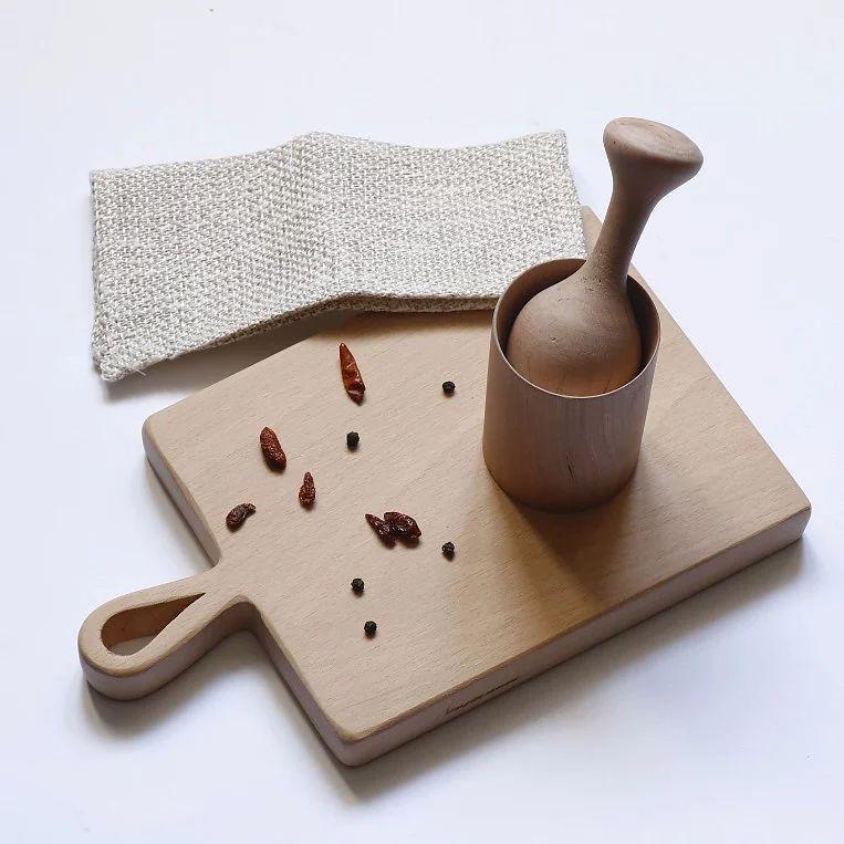 Mortero y maja de madera sobre tabla de cocina