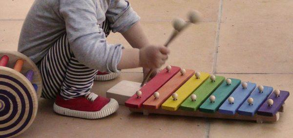 Niño jugando con xilófono de madera