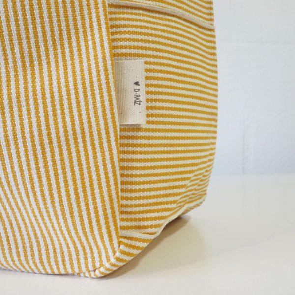 Detalle marca bolso playa de rayas amarillas y blancas