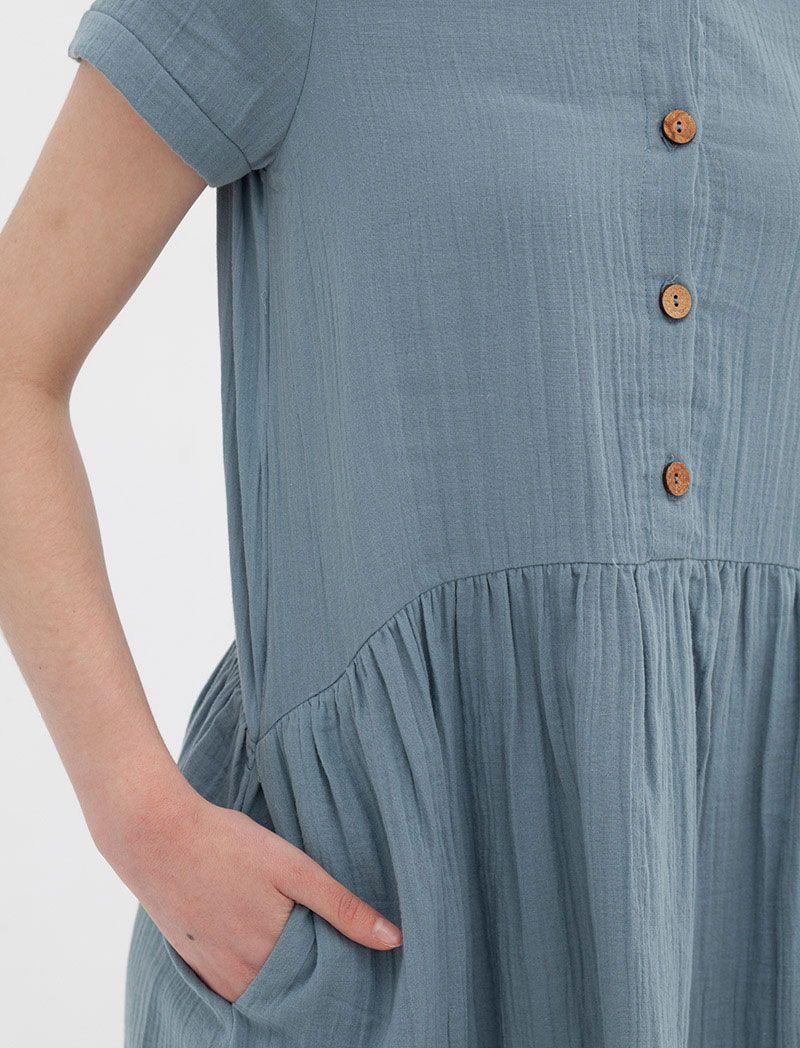 Detalle vestido azul con botones de coco y bolsillos