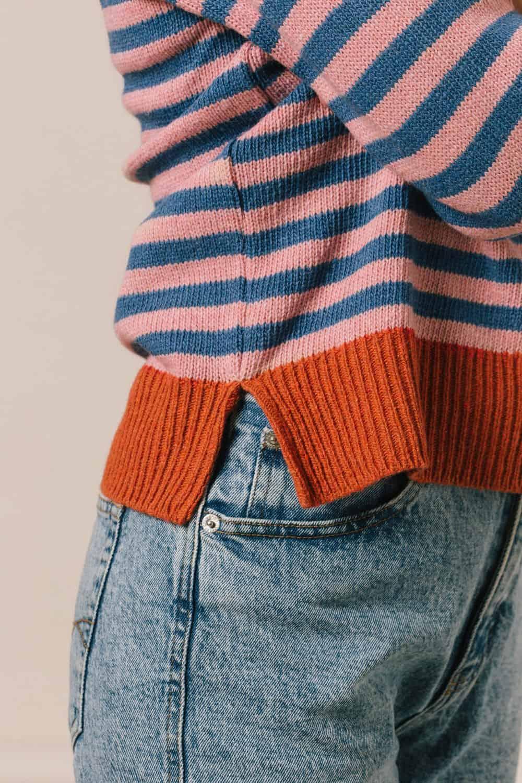 Detalle bajo naranja sweater mujer