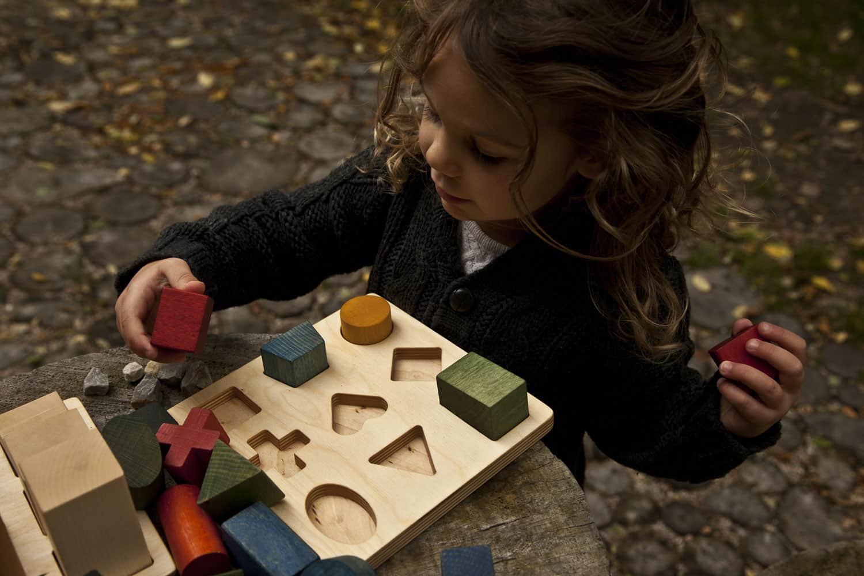 Niña encajando formas geométricas de colores