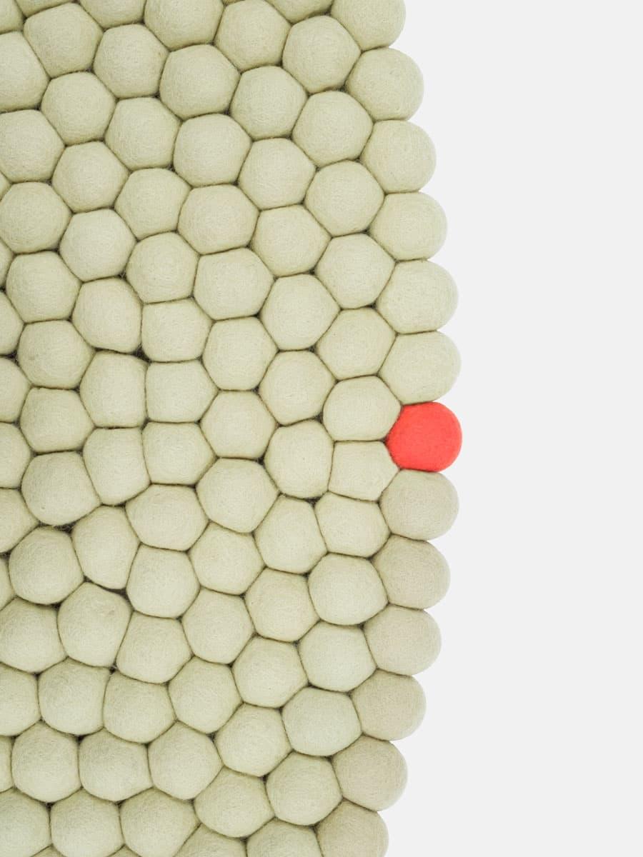 Detalle alfombra circular verde beige con punto salmon