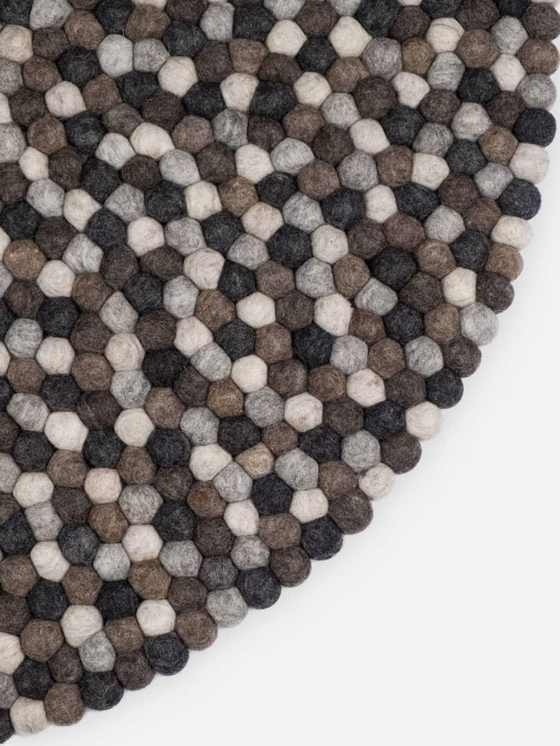 Detalle alfombra redonda bolas natural oscuro