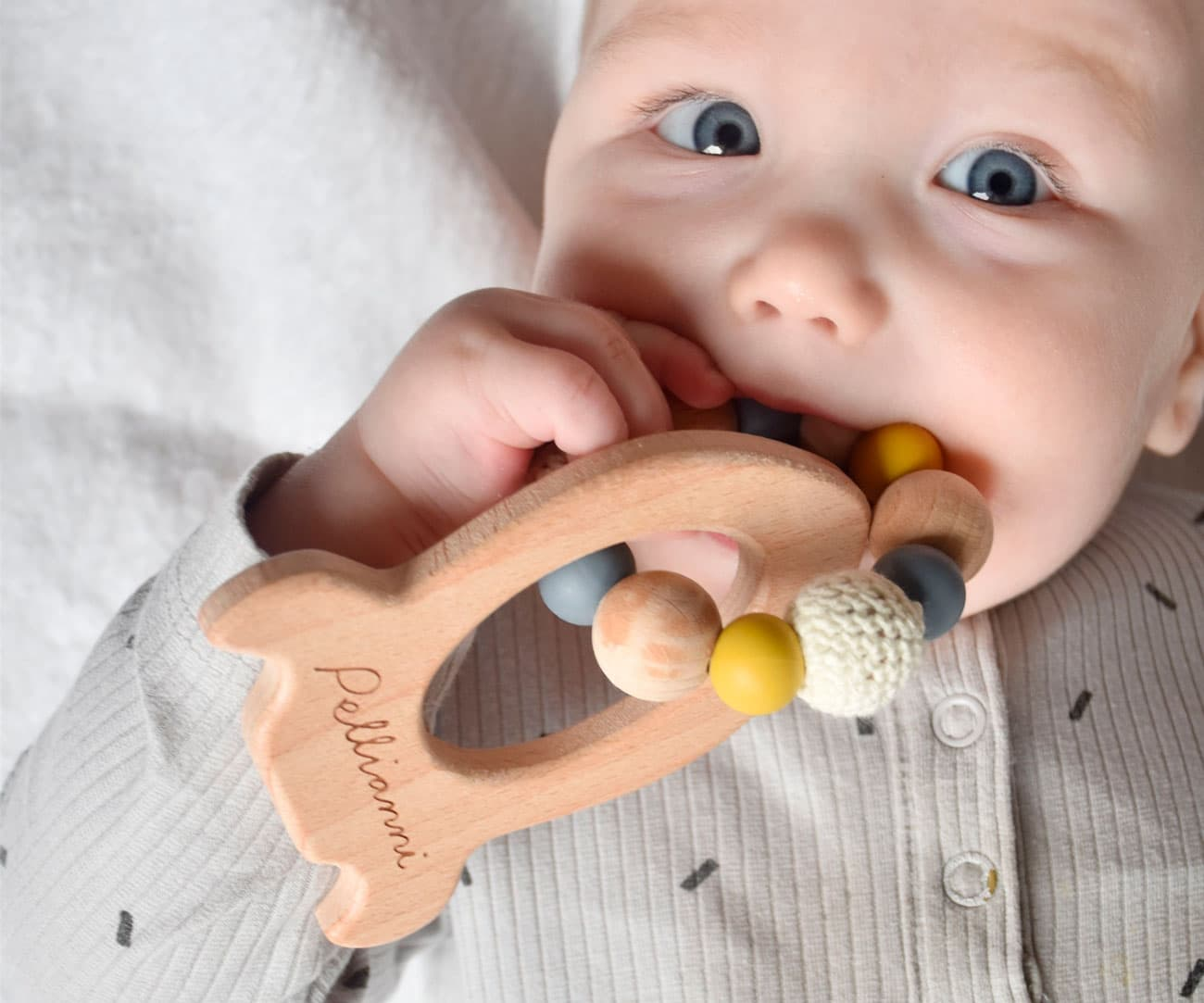 Bebé mordiendo mordedor de madera