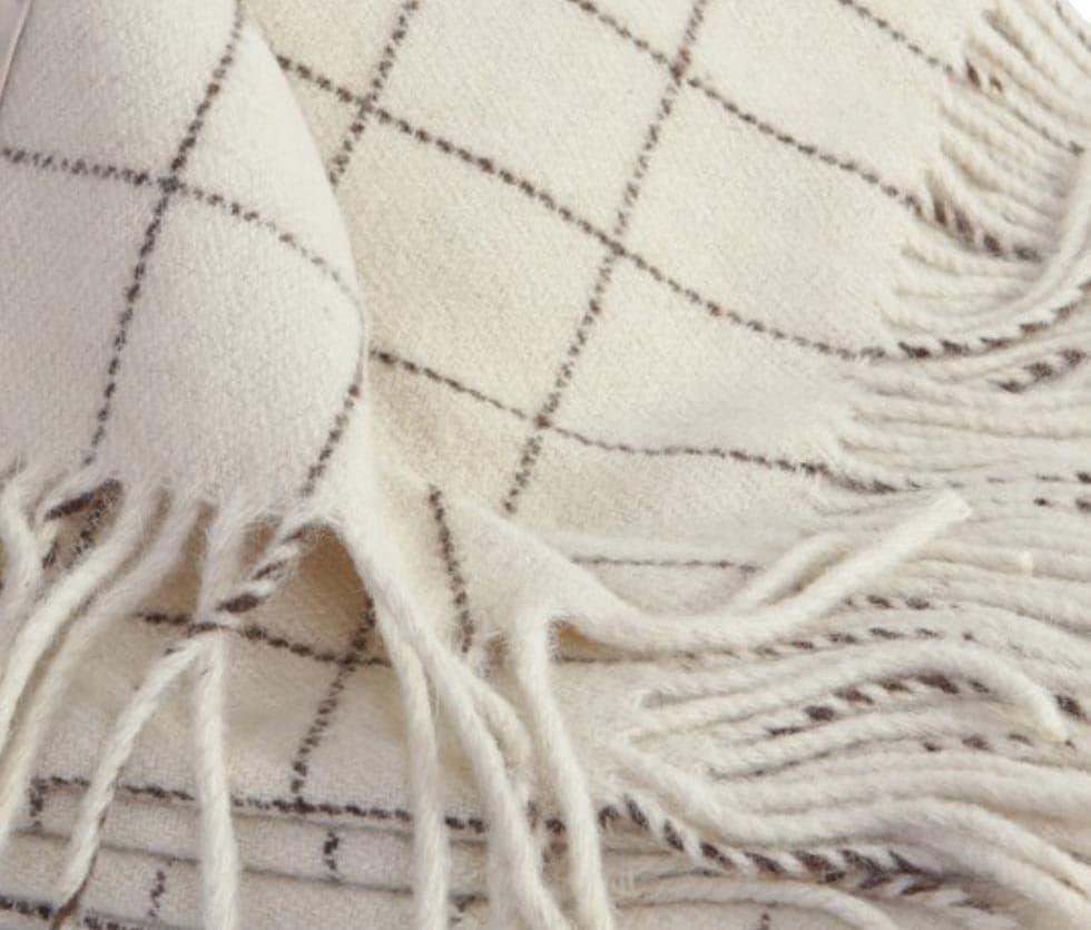 Detalle manta decorativa para cama de cuadros blanca