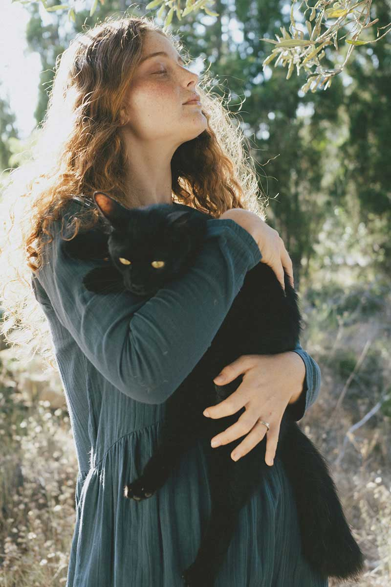 Mujer con gato en brazos vestido ecológico azul